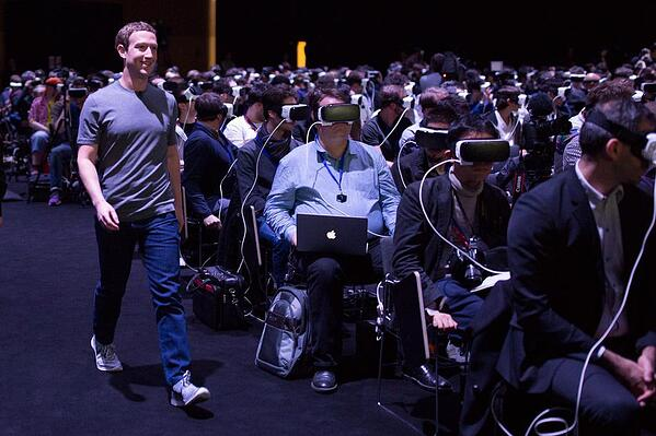 Mark Zuckerberg walking through an audience wearing VR goggles