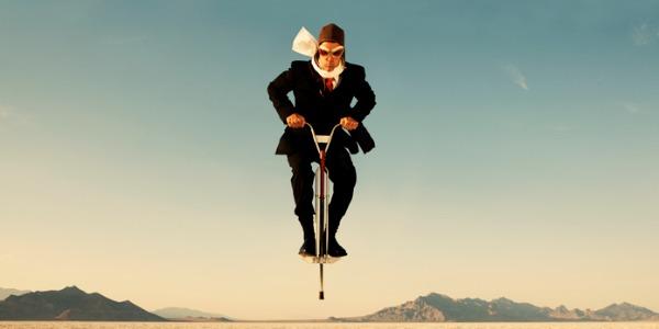 businessman-on-pogo-stick-in-desert-picture-id108347844