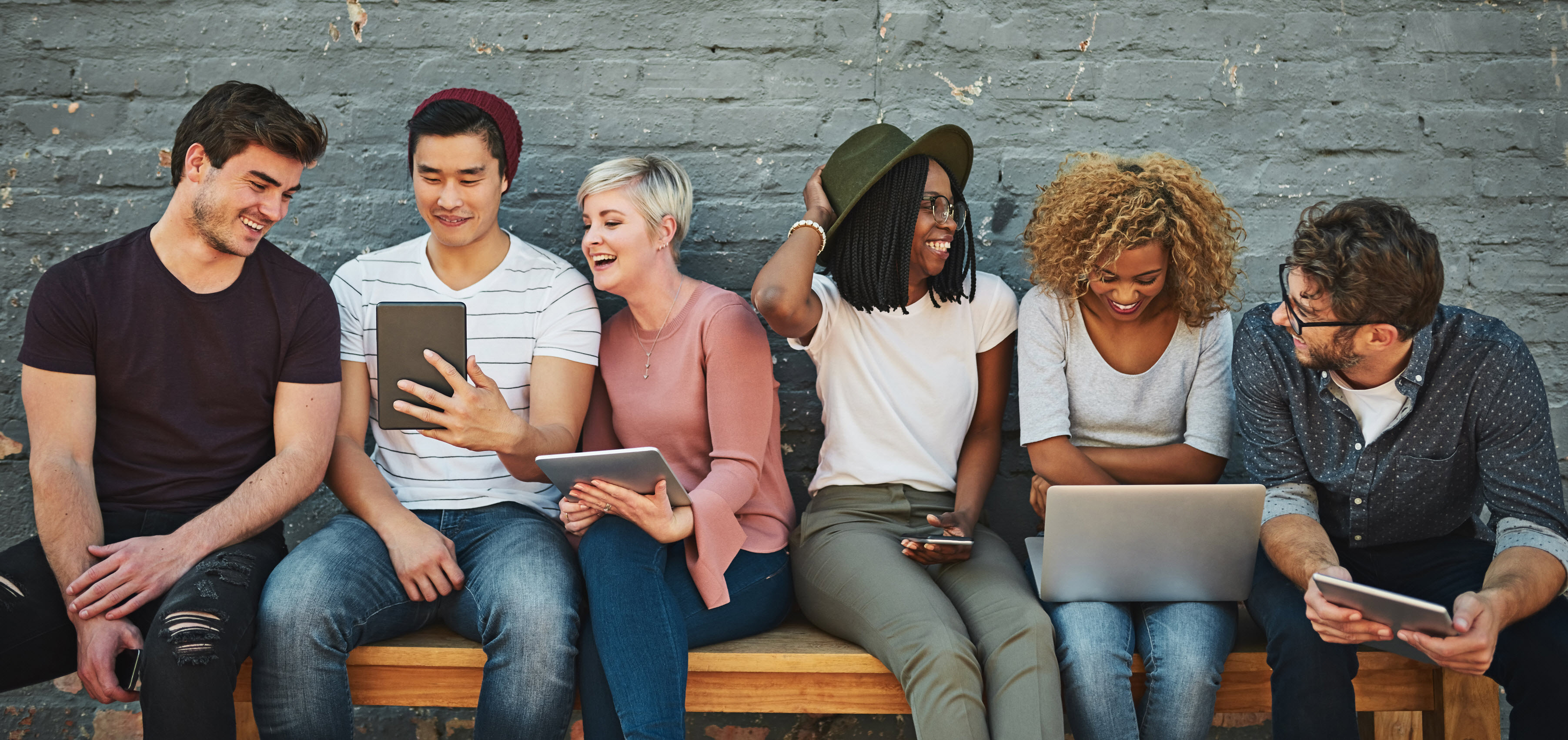 iStock-862201574 young people on bench devices crop